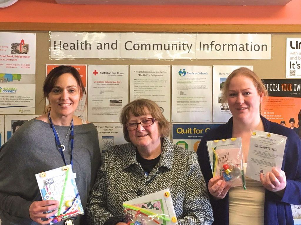 From left,  Alyson Watts (Community Health Social Worker) receiving grounding bags from Advocacy Group members Shirley Williams and Sharleen Fawkner.