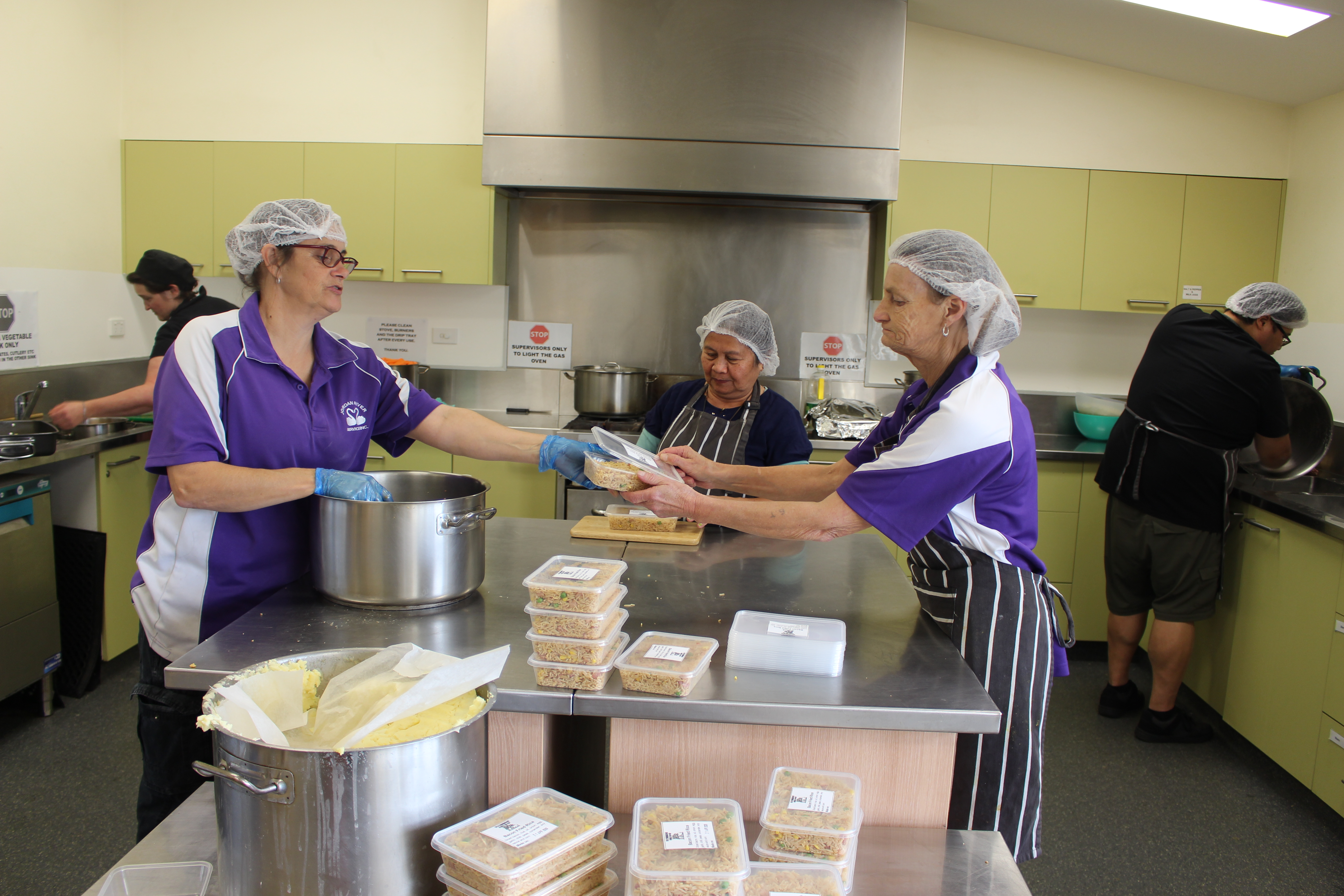 •Tanya Langdon, Lillia Figgel, Cindy Dowling work to get food packed and ready for freezing and delivery.
